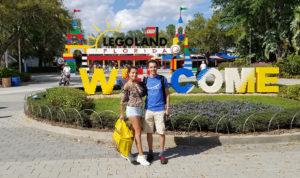 Two Colombians journalists stand in front of the welcome sign at the LEGOLAND Florida Resort in Winter Haven