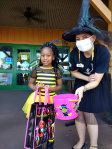 A VIC employee holds a container of candy for a girl dressed as a bee during the VIC's Halloween event