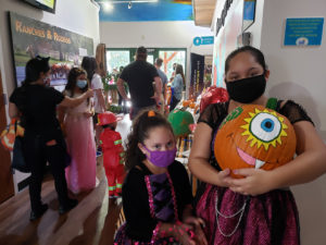 Two young girls in costume hold their pumpkin submission during the VIC's Halloween event