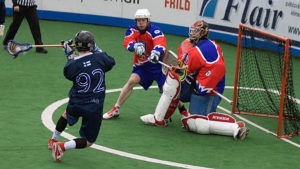 A box lacrosse or indoor lacrosse player prepares to throw the ball toward the goal.