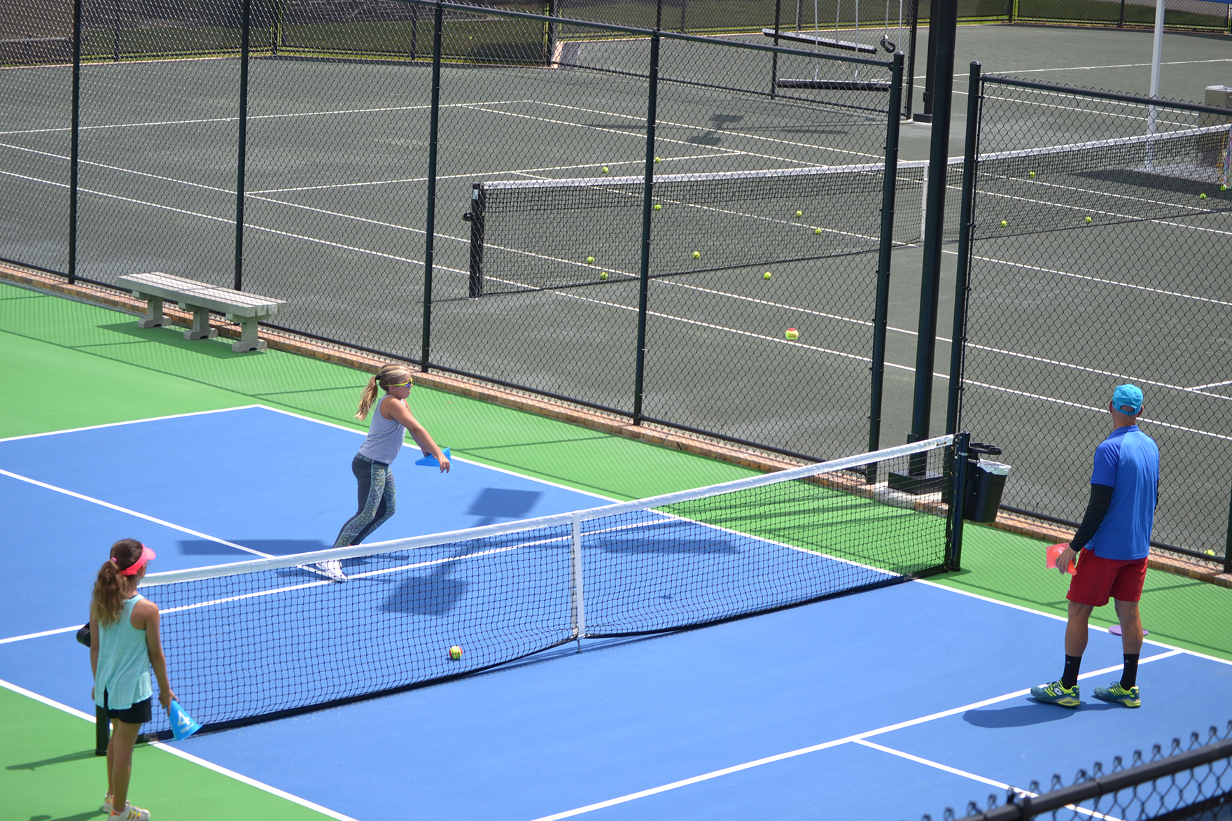 A girl takes a tennis lesson at the courts in Winter Haven.