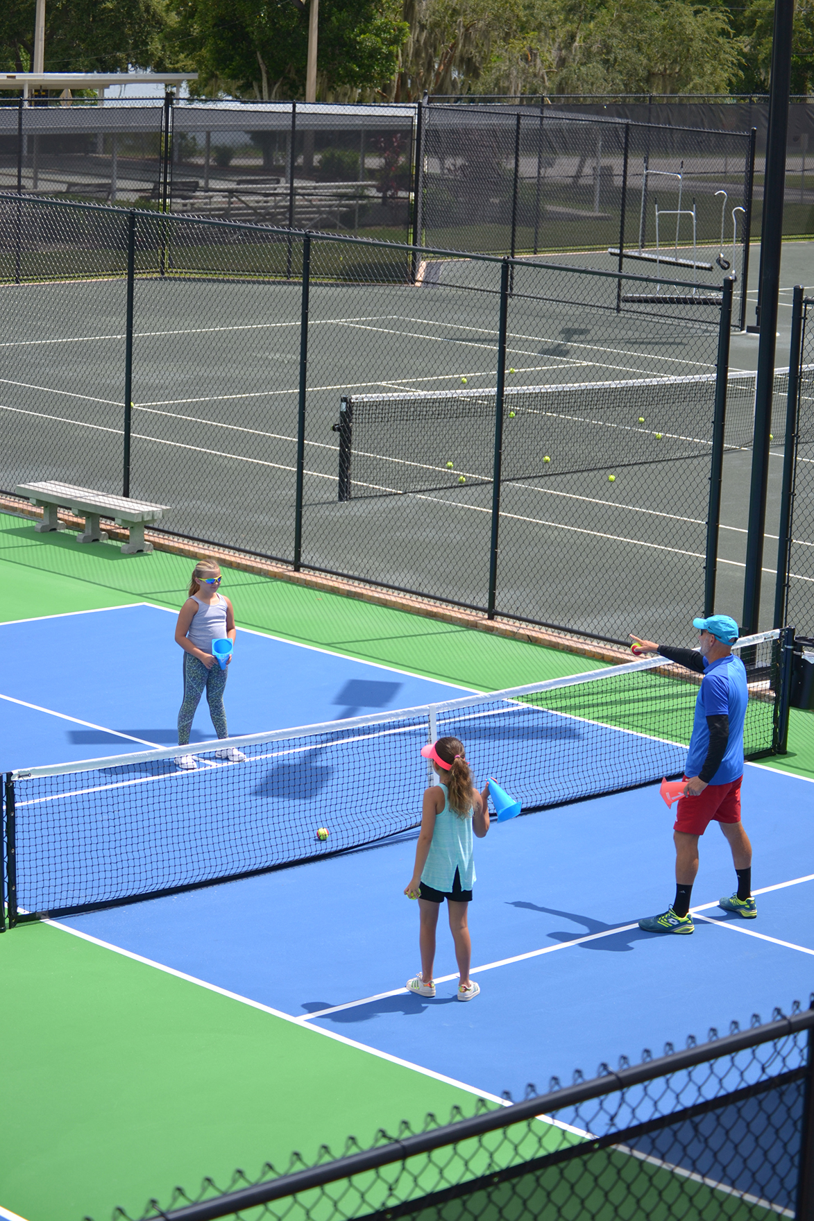 A girl receives instruction during a tennis lesson in Winter Haven