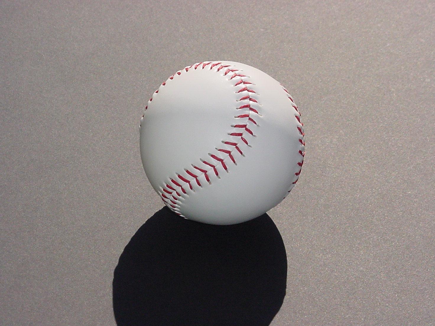 A softball sits on a parking lot