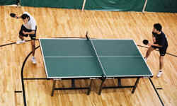 Two players volley during a table tennis match
