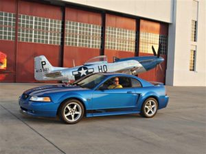 A Ford Mustang is placed in front of an antique plane for this publicity photo