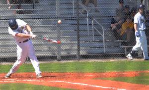 A college baseball player hits the ball during the RussMatt Tournament