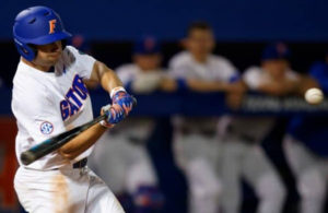 A Gators baseball players swings at a pitch.