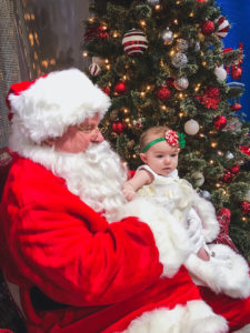 Santa sits with a child on his lap at the Visitor Information Center