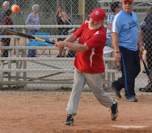A batter hits the ball during a softball game
