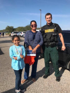 A deputy stands with a mother and daughter at the Visitor Information Center