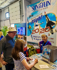 Joni Allen, right, discusses Polk County with visitors to the SUN 'n FUN Aerospace Expo booth at the EAA AirVenture