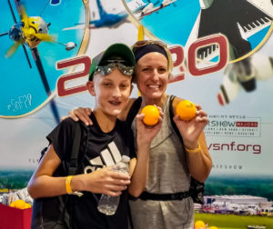 Visitors holding orange squeeze balls in the SUN 'n FUN Aerospace Expo booth at the EAA AirVenture