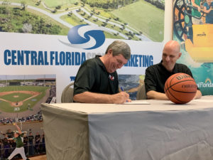 Joe Picket, left, YBOA president, signs the agreement to move YBOA headquarters to the AdventHealth Fieldhouse and Conference Center while YBOA Vice President of Operations Jack Love looks on.