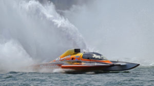 A boat dubbed a grand national hydroplane sends a plume of water into the sky